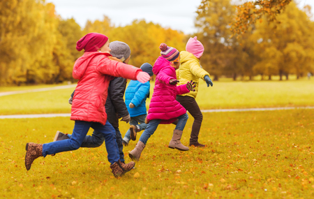 tag: autumn, childhood, leisure and people concept - group of happy little kids playing tag game and running in park outdoors