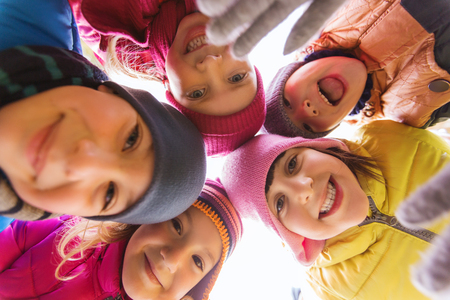 caras felices: la infancia, el ocio, la amistad y el concepto de la gente - grupo de niños felices se enfrenta en el círculo Foto de archivo
