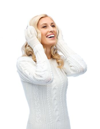 earmuffs: winter, fashion, christmas and people concept - smiling young woman in earmuffs and sweater Stock Photo