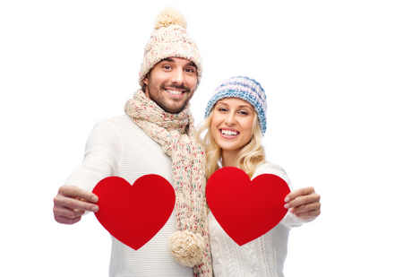 embracing couple: love, valentines day, couple, christmas and people concept - smiling man and woman in winter hats and scarf holding red paper heart shapes