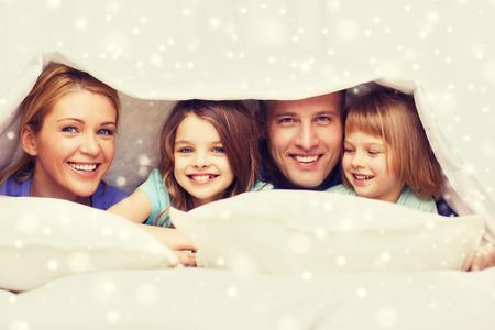 cama: familia, los hijos, la comodidad, ropa de cama y concepto de hogar - familia feliz con dos niños menores de manta más de copos de nieve de fondo