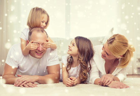 guess: family, childhood, people and home concept - smiling parents with two little girls having fun at home