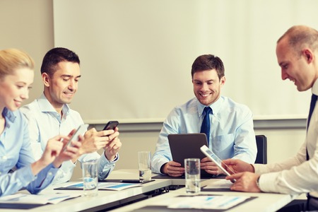 phone business: business, people and technology concept - smiling business team with smartphone and papers meeting in office Stock Photo