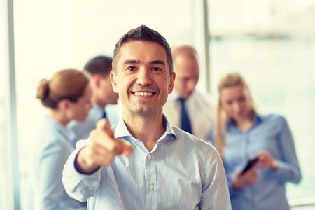 pointing: business, people, gesture and teamwork concept - smiling businessman pointing finger to you with group of businesspeople meeting in office