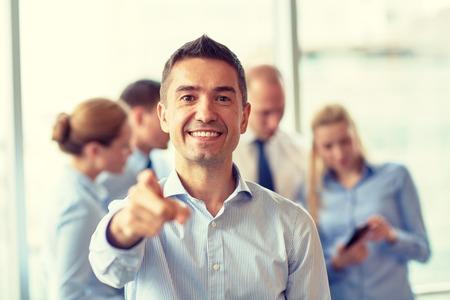 dedo: negocio, la gente, el gesto y el trabajo en equipo concepto - hombre de negocios sonriente dedo que se�ala a usted con un grupo de hombres de negocios reuni�n en la oficina