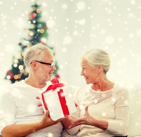 happy seniors: christmas ,family, holidays, age and people concept - happy senior couple with gift box and snow