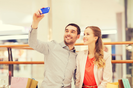 consumerism: sale, consumerism, technology and people concept - happy young couple with shopping bags and smartphone taking selfie in mall
