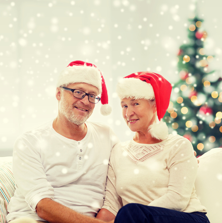 family sofa: family, holidays, christmas, age and people concept - happy senior couple in santa helper hats sitting on sofa at home Stock Photo