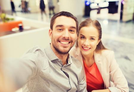 centro comercial: la tecnolog�a, la fotograf�a, y la gente concepto - Pareja feliz teniendo selfie con el tel�fono inteligente o una c�mara en el centro comercial