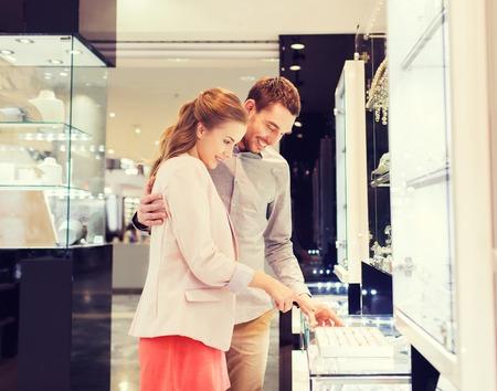 販売、消費、ショッピング街、人々 のコンセプト - 宝石で婚約指輪を選ぶ幸せなカップル ストア モール