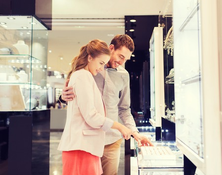 sale, consumerism, shopping and people concept - happy couple choosing engagement ring at jewelry store in mall Imagens
