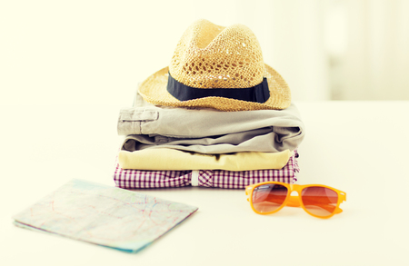 folded clothes: travel, summer vacation, tourism and objects concept - close up of folded clothes and touristic map on table at home Stock Photo