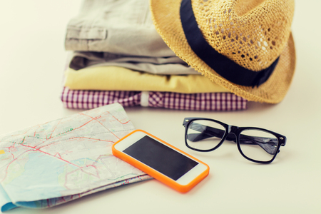 folded: travel, summer vacation, tourism and objects concept - close up of folded clothes, smartphone and touristic map on table at home Stock Photo