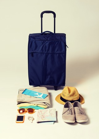 travel bag: summer vacation, tourism and objects concept - travel bag, map, air ticket and clothes with personal stuff