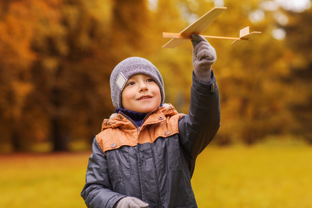 model airplane: autumn, childhood, dream, leisure and people concept - happy little boy playing with wooden toy plane outdoors