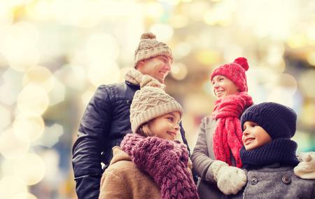 padres hablando con hijos: la familia, la infancia, la temporada, vacaciones y la gente - concepto de familia feliz en ropa de invierno sobre fondo de las luces