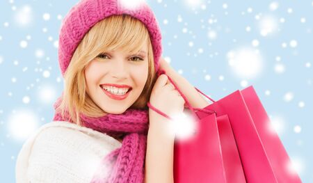 pink hat: winter, people and happiness concept - woman in pink hat and scarf with many shopping bags Stock Photo