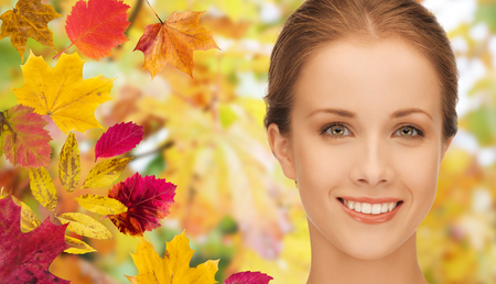 young woman face: beauty, people and season concept - beautiful young woman face over autumn leaves background