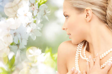 pearl necklace: beauty, luxury, people, holidays and jewelry concept - beautiful woman with sea pearl necklace or beads over cherry blossom background Stock Photo