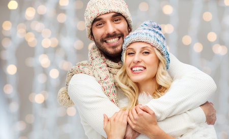 winter, fashion, couple, christmas and people concept - smiling man and woman in hats and scarf hugging over holidays lights background