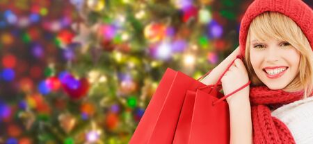 shopper: winter, sale, people and holidays concept - woman in red hat and scarf with many shopping bags over blue lights background Stock Photo