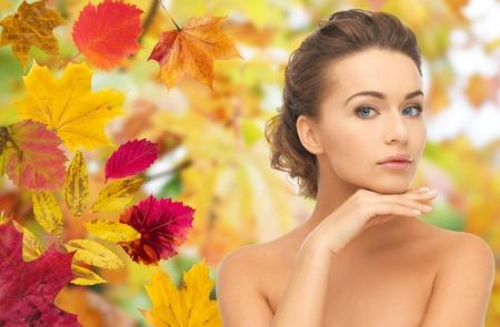 美しさ: 美しさ、人、季節、健康の概念 - 秋に彼女の顔に触れる若い美人葉背景