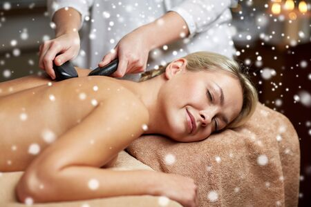 girl care: people, beauty, spa, healthy lifestyle and relaxation concept - close up of beautiful young woman having hot stone back massage in spa with snow effect