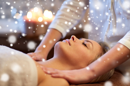 massagist: people, beauty, spa, healthy lifestyle and relaxation concept - close up of beautiful young woman lying with closed eyes and having massage in spa with snow effect
