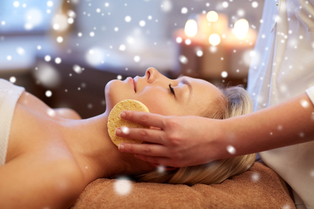 relaxation: people, beauty, spa, skin care and relaxation concept - close up of beautiful young woman lying with closed eyes and having face massage with sponge in spa with snow effect