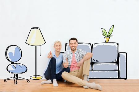 people, repair, moving in, interior and real estate concept - happy couple sitting on floor and showing thumbs up at new home over furniture cartoon or sketch background Foto de archivo