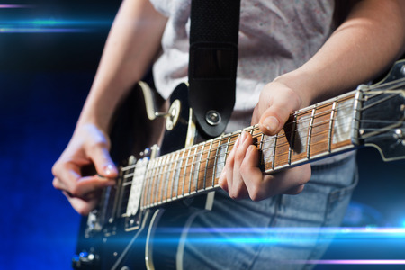 guitar: music, people, musical instruments and entertainment concept - close up female musician hands playing electric guitar with mediator