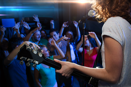 fans: holidays, music, nightlife and people concept - close up of singer playing electric guitar and singing on stage over happy fans crowd waving hands at concert in night club