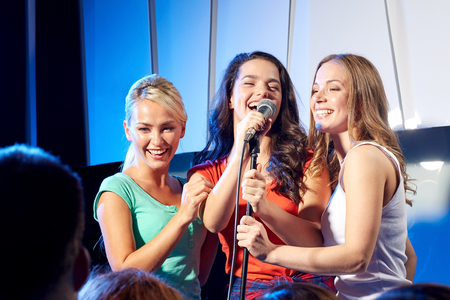 처녀 파티, 가라오케, 음악 콘서트 및 휴일 개념 - 세 가지 행복 젊은 여성 또는 소녀 밴드 나이트 클럽 무대에서 노래 스톡 콘텐츠