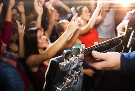 concert: holidays, music, nightlife and people concept - close up of musiciab playing electric guitar on stage over happy people crowd taking picture by smartphones and waving hands at concert in night club