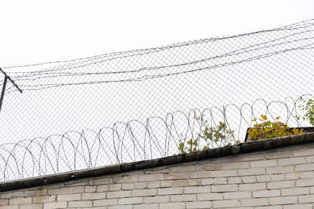 imprisonment: imprisonment, restriction concept - barb wire fence and brick wall over gray sky