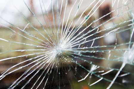 damage, violence, vandalism and danger concept - broken glass with cracks