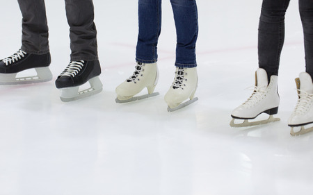 ice arena: people, winter sport and leisure concept - close up of legs in skates on skating rink