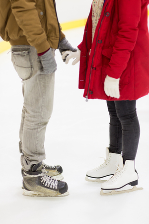 ice arena: people, love, winter and leisure concept - close up of happy couple holding hands and skating on ice rink