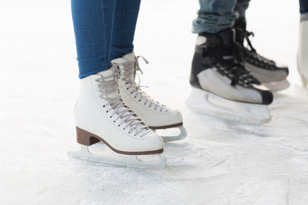 ice skating: people, winter sport and leisure concept - close up of legs in skates on skating rink