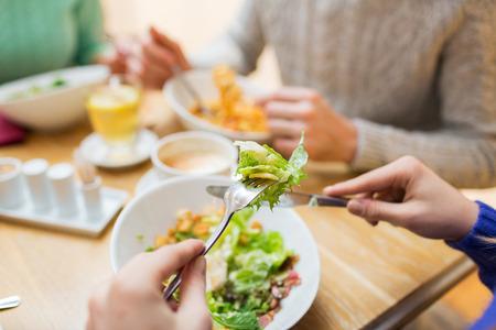 comiendo: gente, el ocio y el concepto de comida - close up amigos cenando y comiendo en el restaurante Foto de archivo