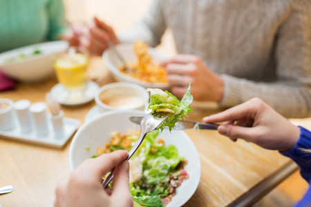 salad fork: people, leisure and food concept - close up friends having dinner and eating at restaurant