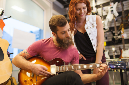 boyfriend: music, sale, people, musical instruments and entertainment concept - happy couple of musicians with guitar at music store