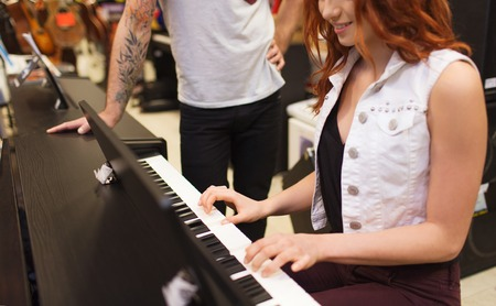 entertainment concept: music, sale, people, musical instruments and entertainment concept - happy man and woman playing piano at music store