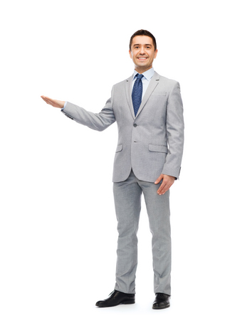 hand pointing: business, people, advertisement and office concept - happy smiling businessman in suit showing something imaginary Stock Photo