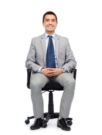 gray suit: business, people and office concept - happy businessman in suit sitting in office chair