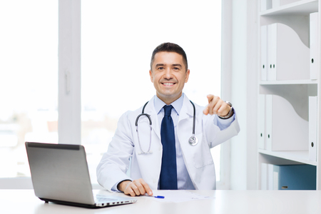health care decisions: profession, gesture, people, technology and medicine concept - smiling male doctor in white coat pointing finger at you in medical office
