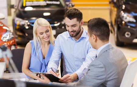 hispanic couple: auto business, sale and people concept - happy couple with dealer buying car in auto show or salon