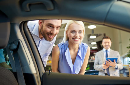 buying a car: auto business, car sale, technology and people concept - happy couple with car dealer in auto show or salon