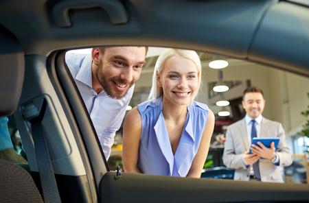carro: negocio de autos, venta de los vehículos, la tecnología y el concepto de la gente - la feliz pareja con distribuidor de coche en salón del automóvil o el salón Foto de archivo