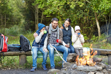 camping, travel, tourism, hike and people concept - happy family sitting on bench and drinking hot tea from cups at camp fire in woods Archivio Fotografico